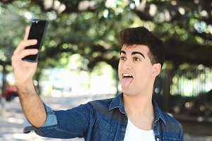Happy young man taking a selfie.
