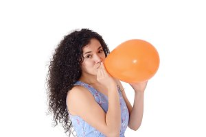 Young latin woman is blowing balloon