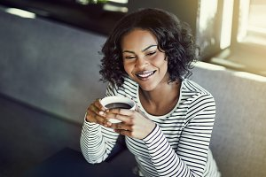 Young African woman smiling and drin