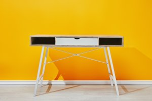 Wooden table near bright yellow wall