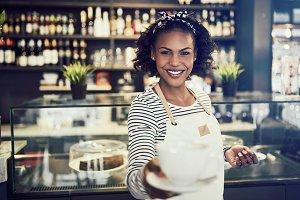 Smiling cafe waitress holding up a f