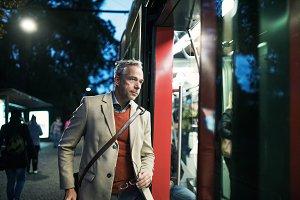 Mature businessman getting on a tram