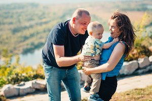 Happy family with baby son on nature