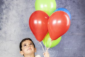 Cute kid holding a lot of balloons
