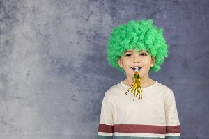 Little boy with a green wig isolated