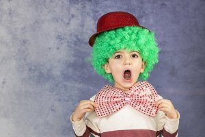 Little boy with a green wig, red hat