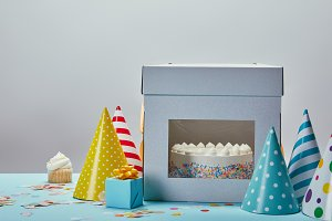Birthday cake, party hats, gift and