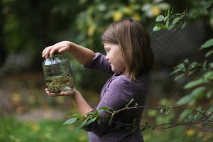Child girl holding jar with frog