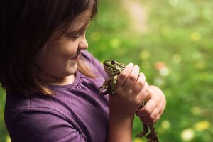funny child girl with frog in hands