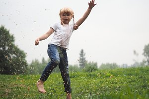 A child jumping in a puddle. The