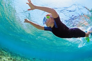 Child in snorkeling mask dive