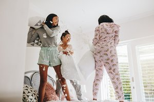 Girls pillow fighting standing