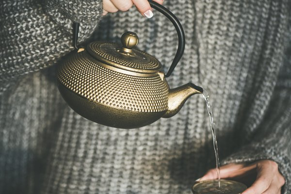 Female pouring green tea from pot