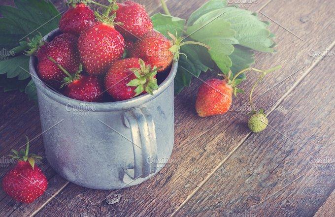 Ripe strawberries in a metal mug. Old wooden table. - Food & Drink