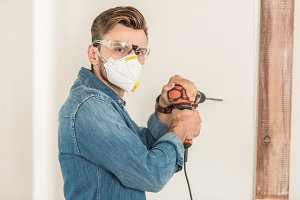 young man in protective workwear usi