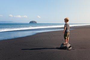 Child stand on black sand beach