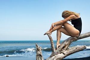 Girl sit on snag  on black beach