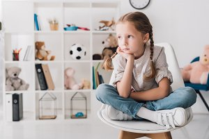 lonely little child sitting on chair