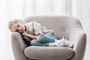 depressed little child lying in armc
