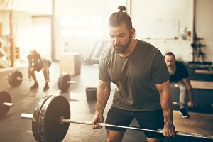 Fit young man weightlifting during a