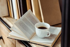 close up of open book with cup of co