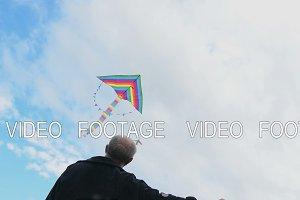Senior man flying kite, view against