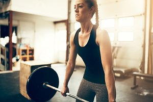 Fit young woman lifting weights duri