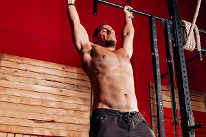 Athletic young man doing pull ups ex