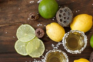 tequila lime and lemon on a wooden t