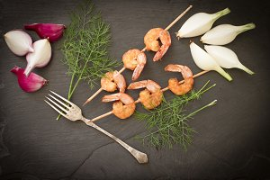 Grilled shrimp with dill on a black