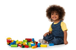 Cute curly girl playing with blocks