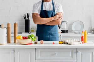 handsome man in apron with arms cros