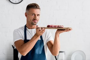 adult smiling man holding steak on c