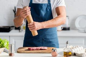 cropped view of man seasoning meat f