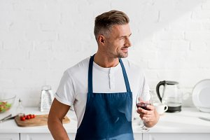 man in apron with glass of wine cook