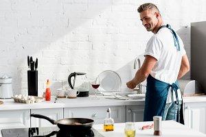 adult man washing dishes at kitchen