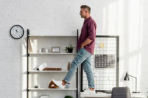 man stepping from desk at home offic