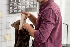 man putting book in bag at desk at h