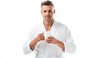 smiling man in bathrobe holding coff