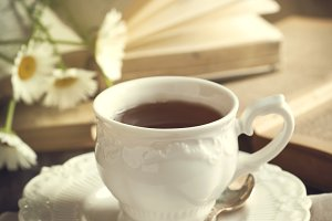 Cup of tea, books and chamomiles
