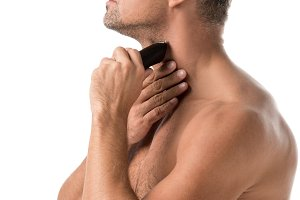 side view of adult man shaving with