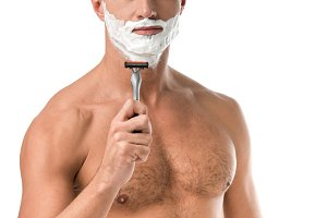 adult man with foam on face shaving