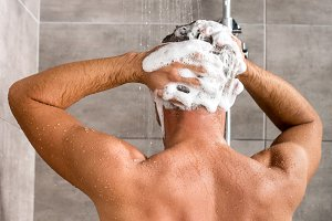 back view of man washing hair with s