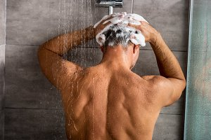 rear view of man washing hair with s