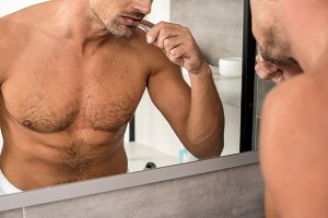 partial view of adult man brushing t