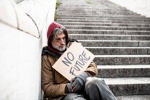Homeless beggar man sitting outdoors
