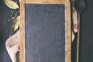 Black board, wooden spoon and spices