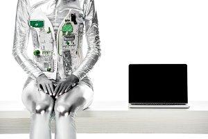 cropped image of robot sitting on ta