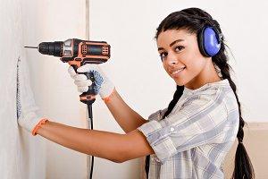 beautiful young woman drilling wall
