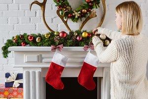 young woman adjusting christmas baub